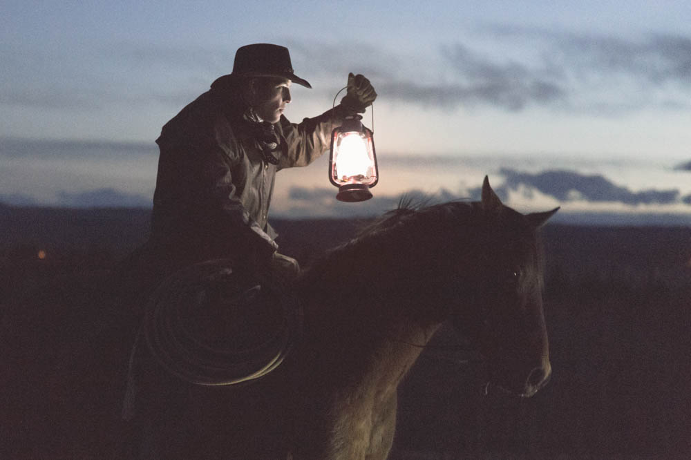 Image of a cowboy on a horse holding lantern in low light