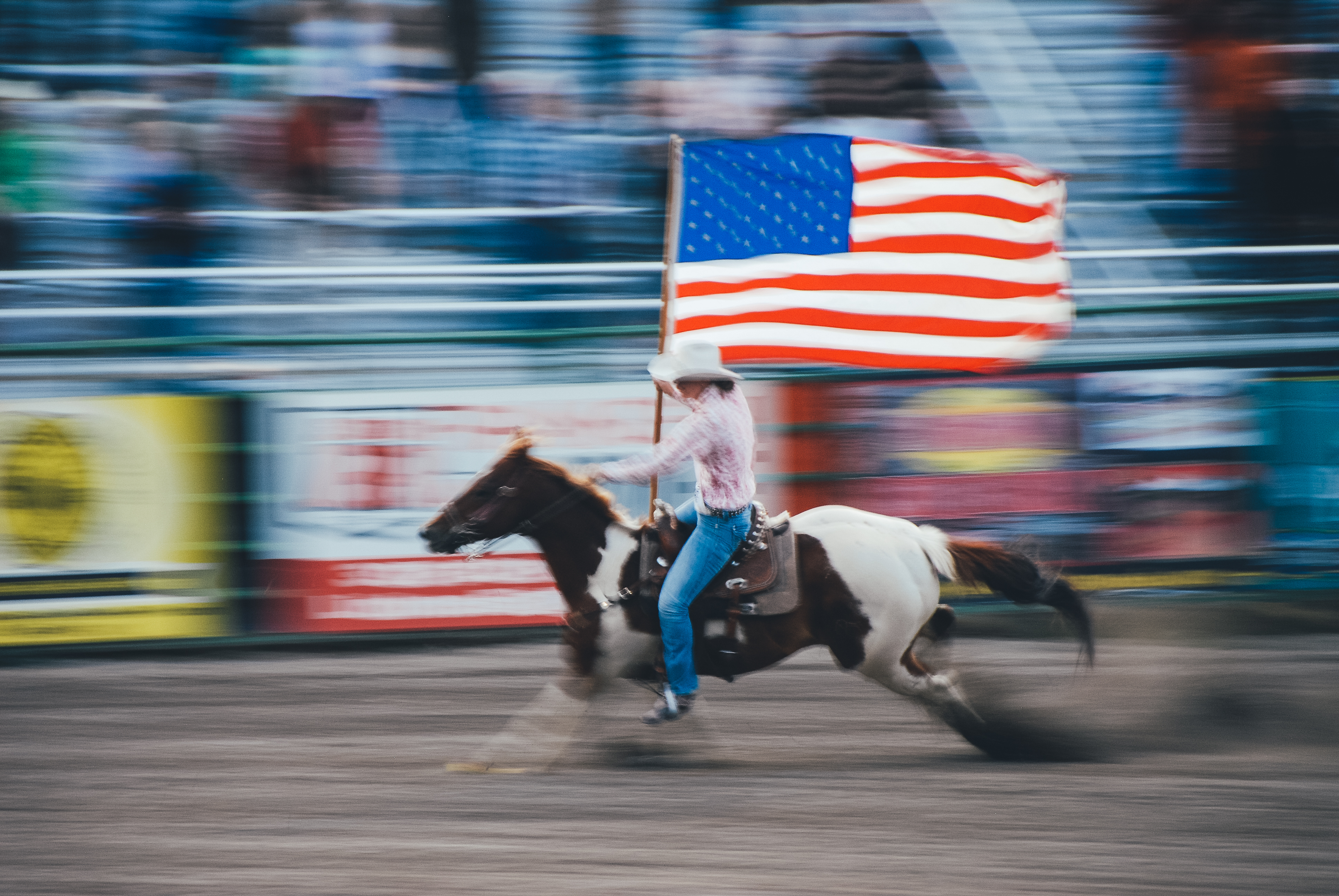 Image utilizing slow shutter speed and panning of a cowboy on a horse with an american flag
