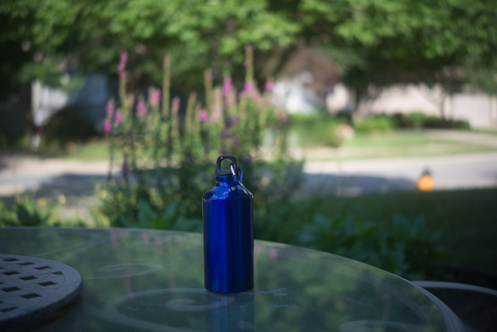 Picture of a blue metal water bottle outside on a table to show thin depth of field at wider apertures