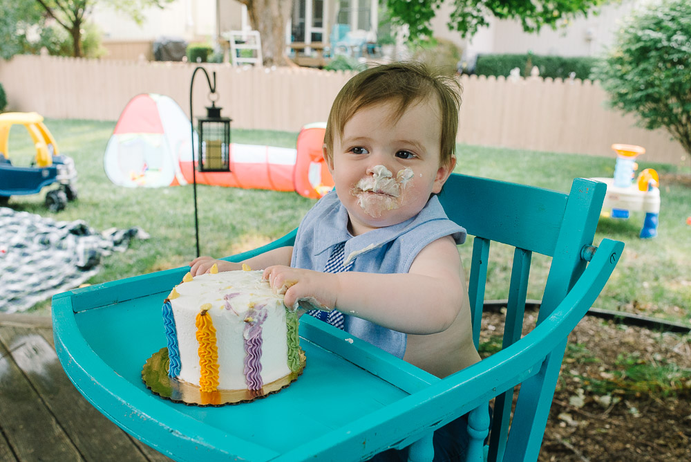 image of a one year old eating birthday cake for the first time as an example about one year old birthday photography