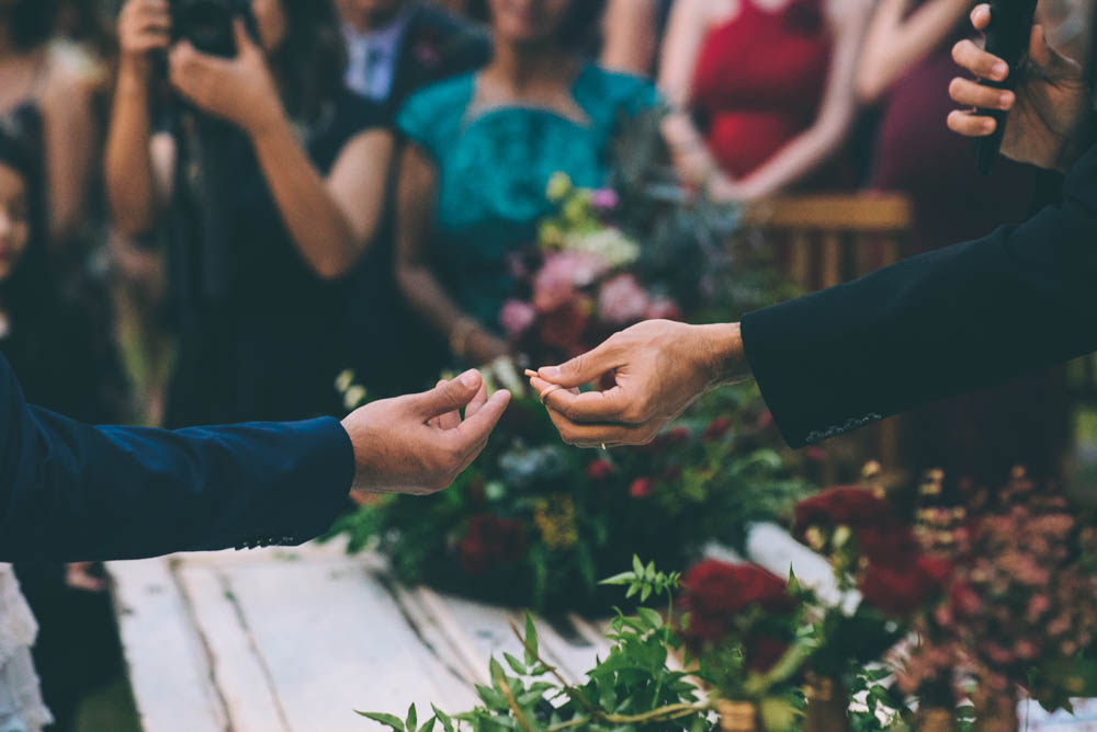 image of a priest handing a groom a wedding ring, a good reason to shoot with two cameras for wedding photography