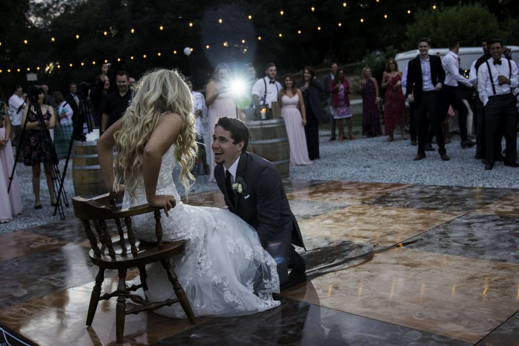 Photo of a bride and groom looking at each other and laughing on the dance floor of their wedding reception