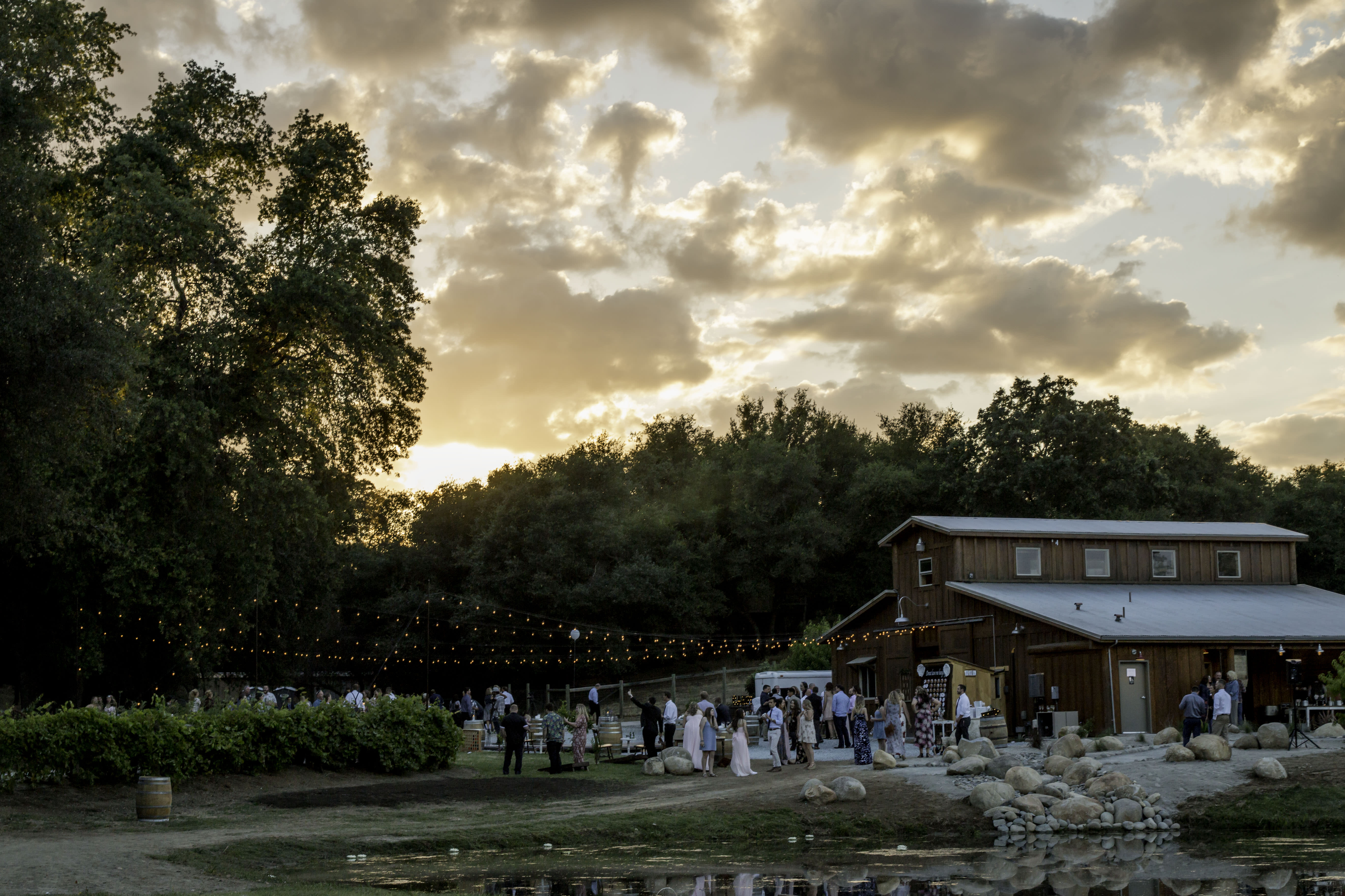 Image from far away showing an outdoor wedding reception at a barn showing how to get into wedding photography
