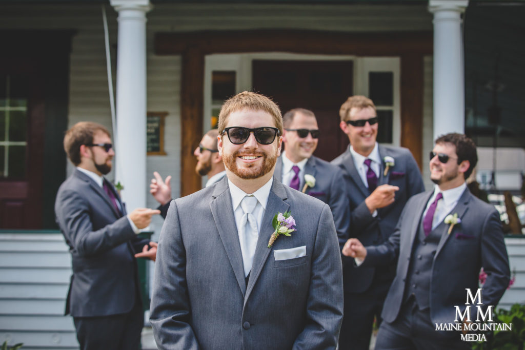 Wedding photography image by Paul Friedman showing a groom wearing his suit and sunglasses with his groomsmen behind him